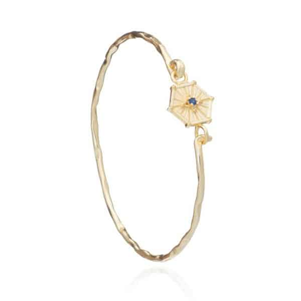 Gold plated brass sprung hexagon charm bangle with tiny iolite gemstone, by Azuni London.