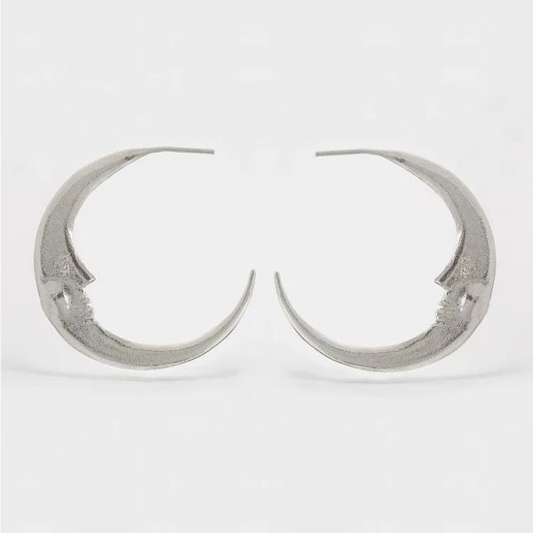 Sterling silver crescent moon hoops with doubled side face details, handmade by Manom Jewellery.