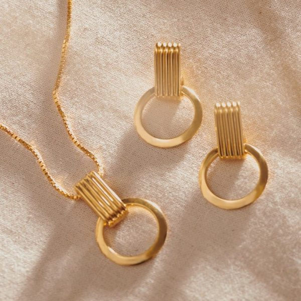 Close up shot of matching Rachel Jackson Eternity Circle Necklace and Eternity Circle Earrings in gold.