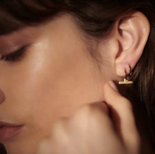 Close up shot of model wearing Rachel Jackson gold plated silver mini t-bar huggie hoops