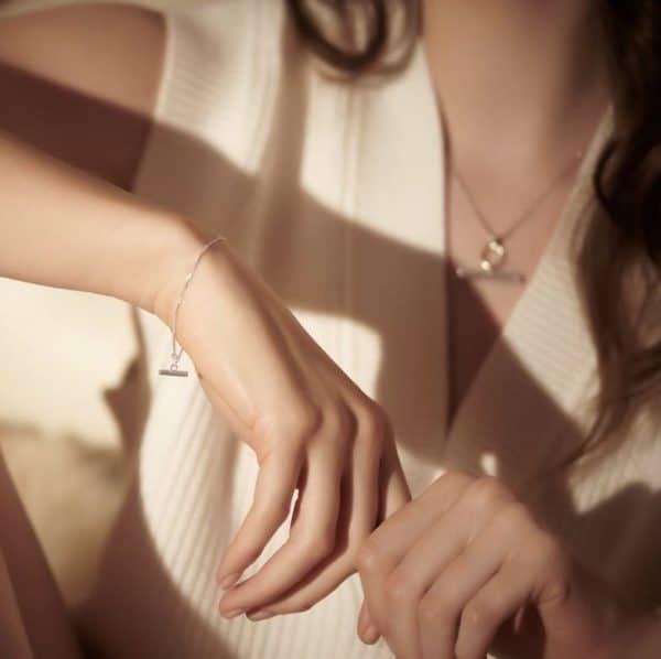 Close up shot of model wearing Rachel Jackson silver mini t-bar bracelet