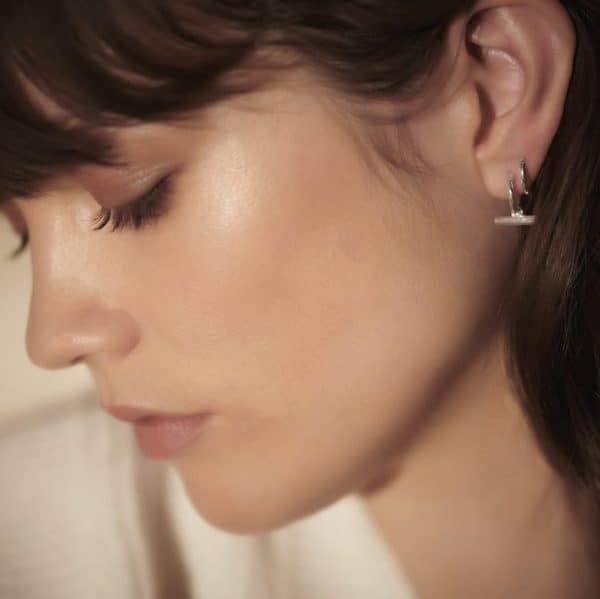 Close up shot of model wearing Rachel Jackson silver mini t-bar huggie hoops