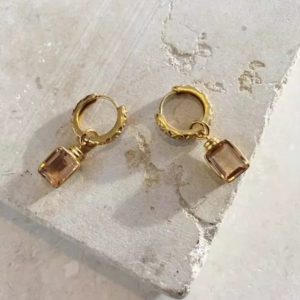22ct gold plated sterling silvver huggie hoops with engraved details and a square champagne coloured glass charm, by Shyla Jewellery