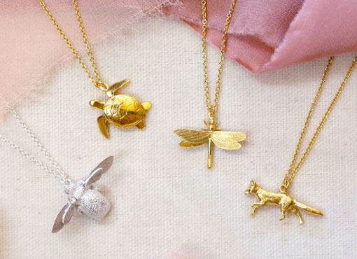 A collection of Alex Monroe necklaces in silver and gold. A detailed bumble bee, a turtle, a dragonfly and a fox necklace decorated with ribbon.