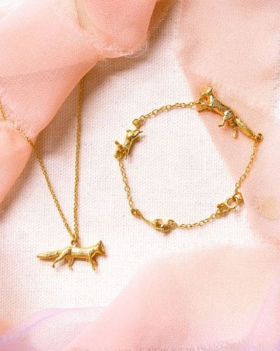 A gold fox necklace and bracelet from Alex Monroe with pink silk ribbon around it.