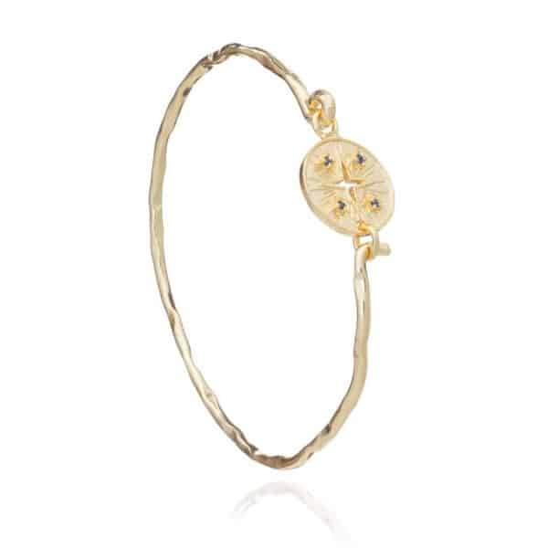 24ct gold plated brass sprung bangle with a coin clasp featuring a cygnus constellation design and four tiny iolite gemstones, by Azuni London