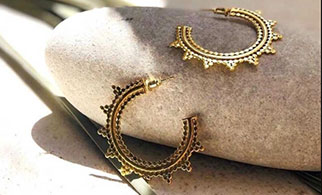 Gold Hoops from Azuni jewellery laying on a pebble