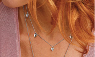A close up of a lady wearing a silver heart necklace from Kit Heath Jewellery
