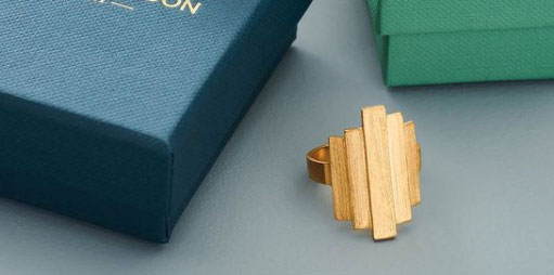 Pernille Corydon Brick ring in gold sitting with branded jewellery boxes
