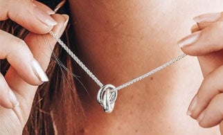 A close up of a lady holding a silver eclipse necklace from Scarlett Jewellery