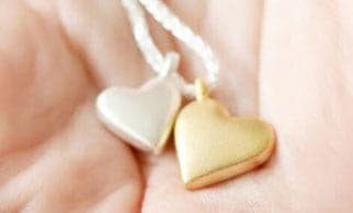 A silver and gold heart necklace from Tales from the earth in a hand