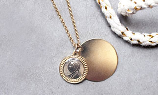A gold necklace from Medecine Douce laid on a concrete backdrop with a bit of rope