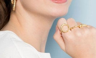 A girl wearing rings and earrings from PURE by Nat