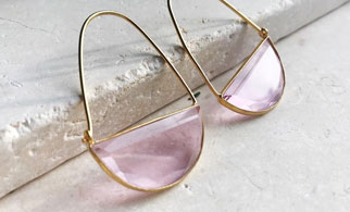 Pink and gold hoop style earrings resting on a concrete tile