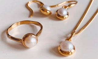 A Gold and pearl ring, necklace and earrings from Luceir placed on a white background