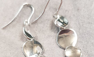 A close up of triple circle disc earrings from the Silverado jewellery collection on a grey felt background
