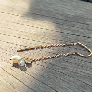A single gold Sea chain earring from Pernille Corydon laying on a piece of wood