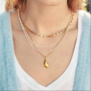 Lady wearing gold seashell necklace by Pernille Corydon