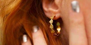 Close up of Rosie Kent gold shell hoop earrings with her hand pushing back her hair away from her ears
