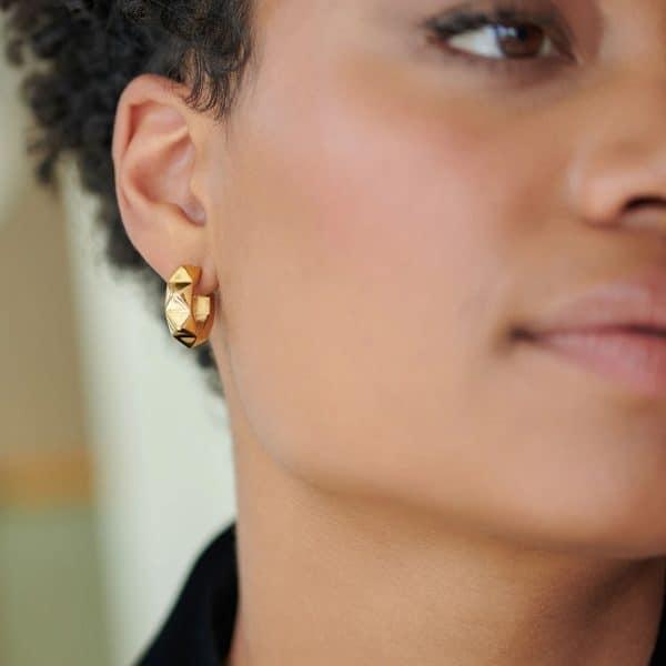Model wearing rachel jacksons gold chunky spike hoop earrings
